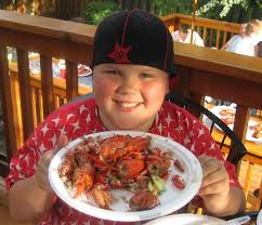 brave kid eating straight tail crawfish